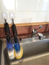 I hate wet sponges, so hair ties keep dish wands hanging and dry.
